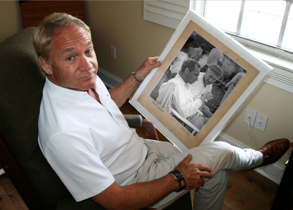 "KC Schulberg holds a photo of his uncle and father on the set of ""Wind of the Everglades"" in 1958 (Photo credit Randall Kenneth-Jones)"