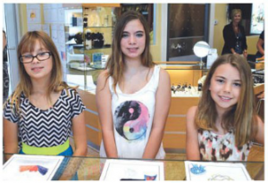 Winners Alyssa Lynn, Paige Godfrey and Destiny Ann Neri has pendants made from their drawings by Classic Creations owner Evan Duke. Photo by Debbie Flessner