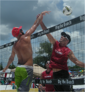 Shirtless Diogo Sousa (26) of Deerfield Beach Florida spikes a ball over the head of his opponent in a Men's Open/Pro (Professional Level) division quarterfinal match.