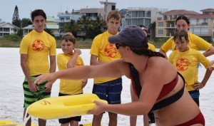 Assistant director, lifeguard Stephanie Ganey instructing Jr. Lifeguards, Nolan Houghton (15), Cooper Middleton (10), Matthew and Alex Liebel, and others how to rescue a simulated victim utilizing two lifeguards with can buoys.