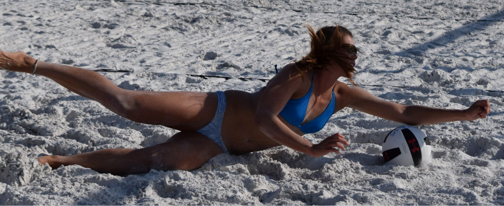 Halie Werkmeister 20, of Springhill Florida, lands in the soft powdery white sand of Siesta Beach, as she dives and stretches as far as she can for a dig in a Women's Open-Division match.