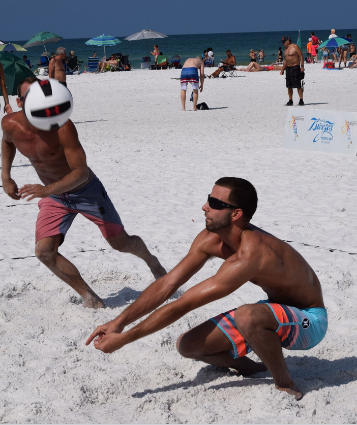 Jonathan Sousa 21, of Coral Springs sets up his partner Kevin Ellis 26, of Pompano Beach during a Pro-Division men's pair match at the Dig The Beach Volleyball Tournament on Siesta Key.